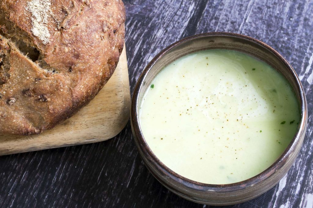 fennel and potato soup in bowl with loaf of brown bread on board