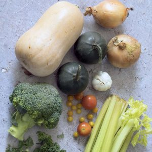 October seasonal vegetables - squash, broccoli, kale, celery, tomatoes, onions, garlic - on grey background