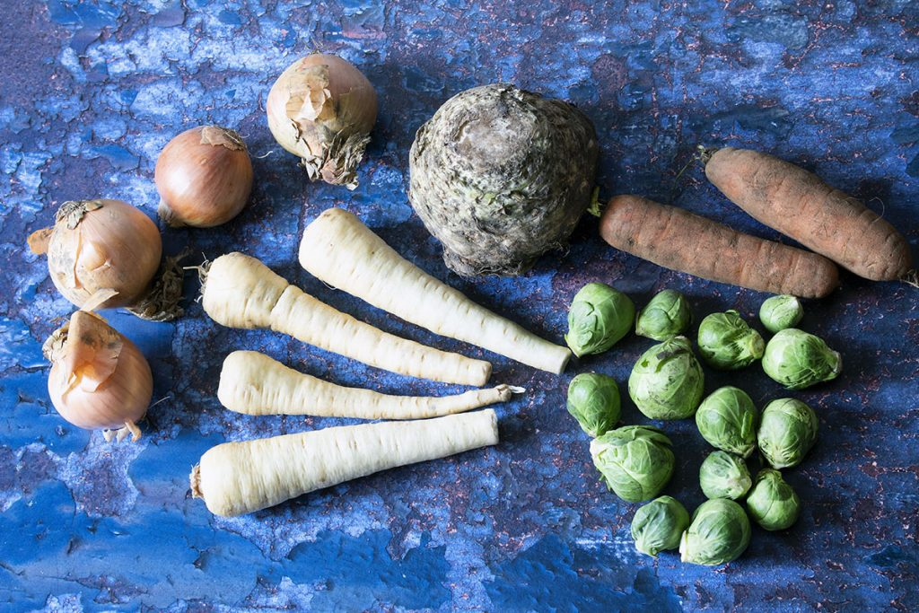 A selection of December seasonal vegetables onions, parsnips, celeriac, brussels sprouts and carrots on metal background