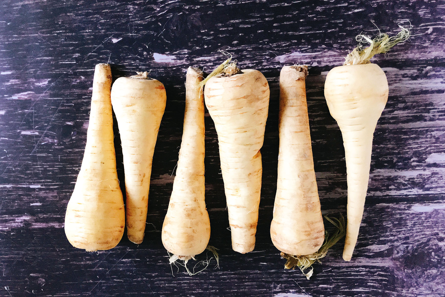 six parsnips on wooden background