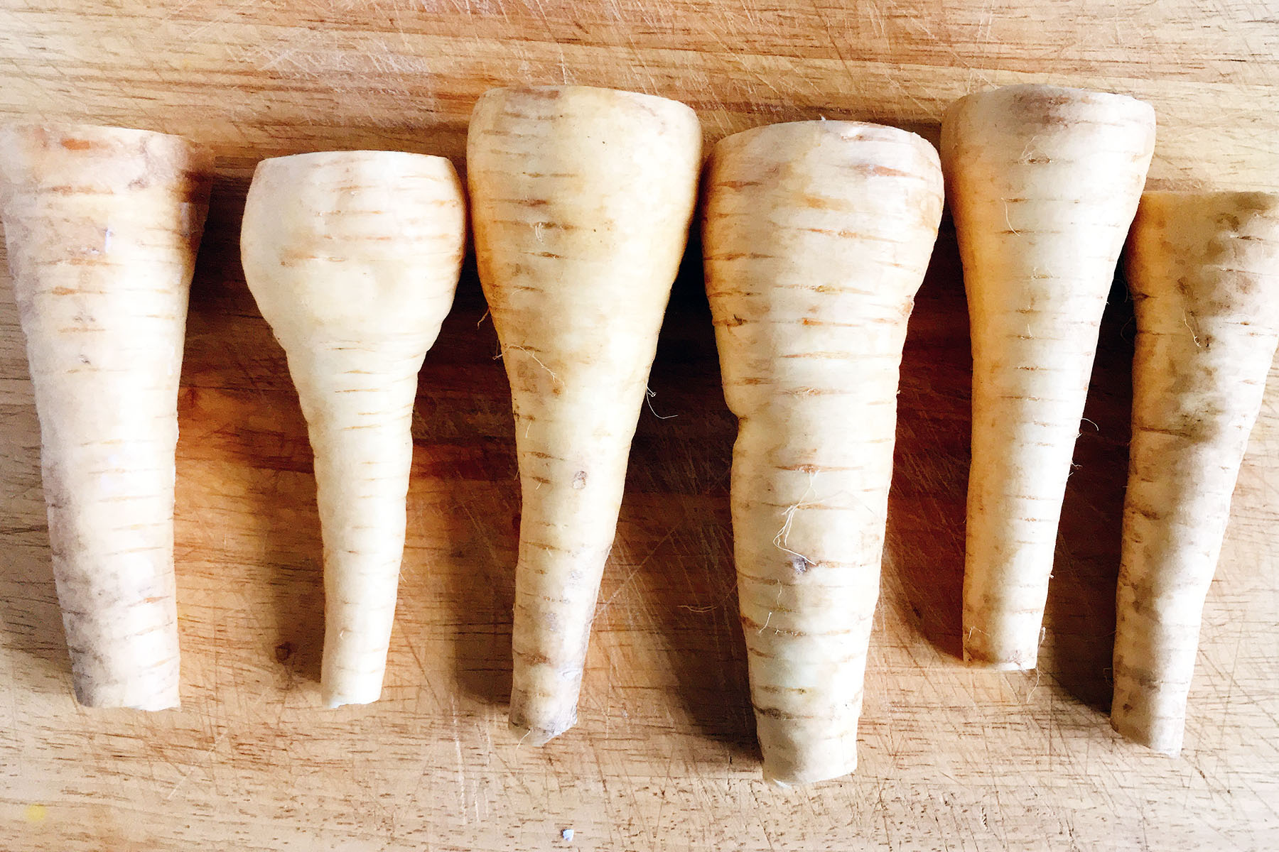 six parsnips on board topped and tailed