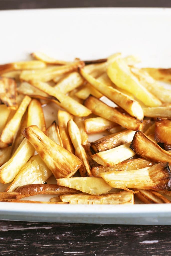 roasted parsnips in a blue and white roasting tin