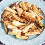 close up of roast parsnips on green plate