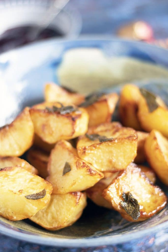 roasted potatoes with sage in blue bowl