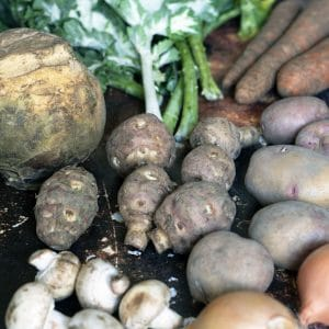 swede, kale, potatoes, carrots, jerusalem artichokes, mushrooms and onions on brown background