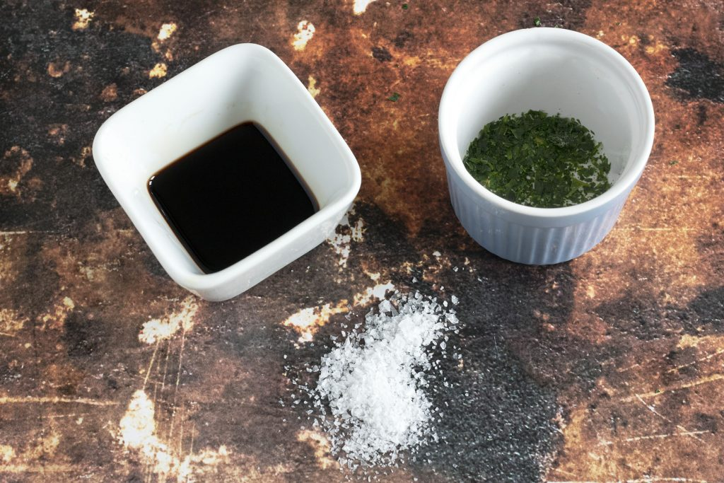 balsamic vinegar, sea salt and chopped parsley on brown background