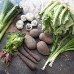 March seasonal vegetables - leeks, mushrooms, radish, cauliflower, potatoes, carrots, spring onions on brown background