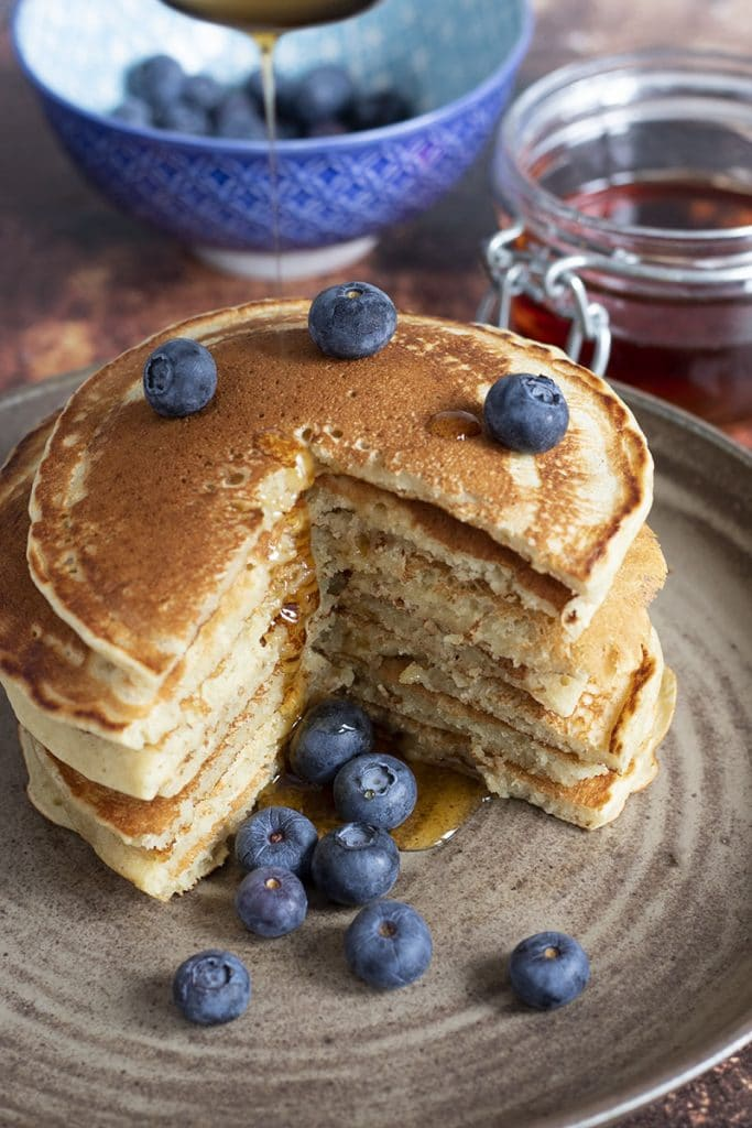 stack of pancakes with blueberries on ceramic plate
