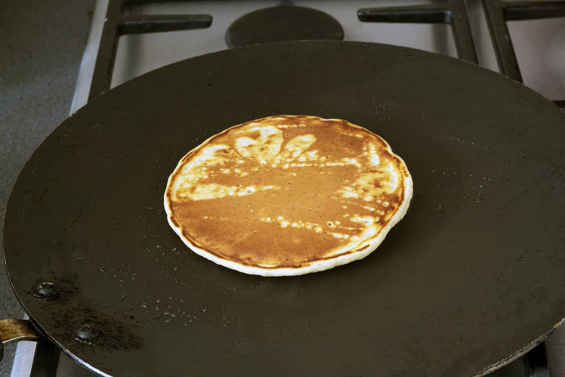 pancake cooking on frying pan over gas hob