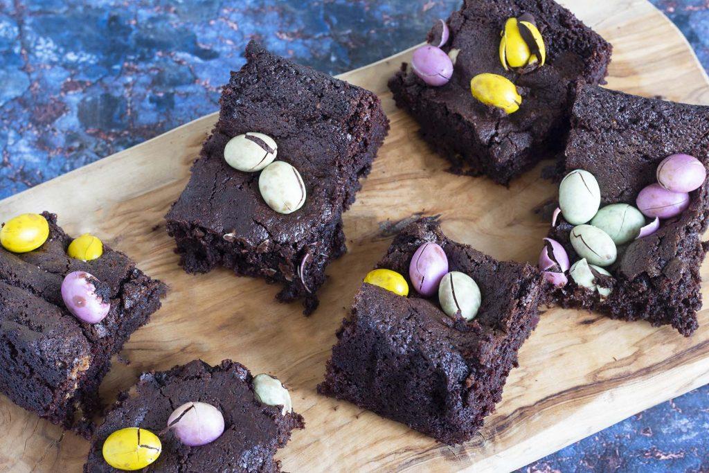 vegan mini egg brownies on board and blue plate