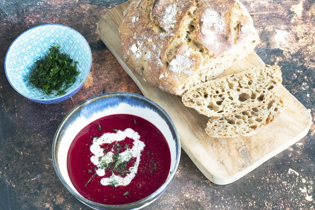 overhead shot of beetroot soup with bowl of dill and loaf of bread