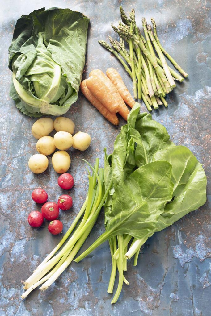 overhead shot of carrots, spring greens, new potatoes, asparagus, spring onions, radish