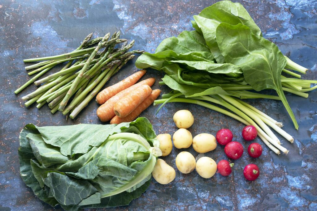 Seasonal vegetables in May spring greens, potatoes, spring onions, radish, carrots, asparagus and spinach