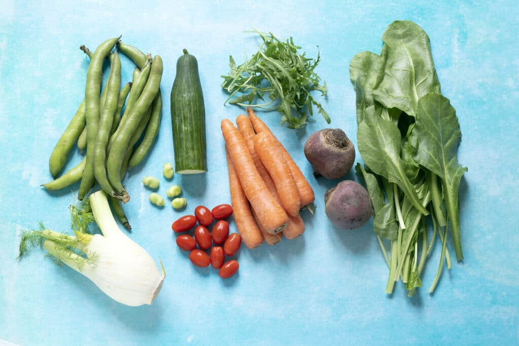 flatlay on blue background of vegetables that grow in the UK in June - fennel broad beans, cucumber, tomatoes, carrot, rocket and spinach